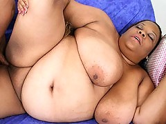 Black whore massaging her heavy huge tits on the couch